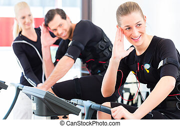 Coach giving ems training lessons - Female coach giving man...