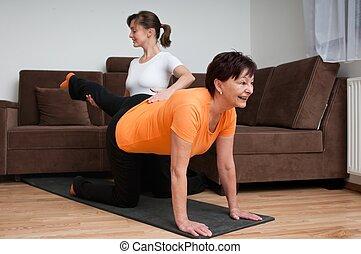 Coach helping senior woman exercising