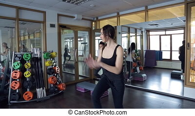 Coach helps to do exercises on fitness stepper in sport studio
