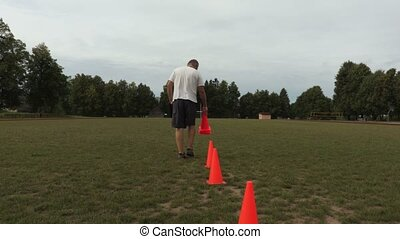 Coach places red cones on the football field