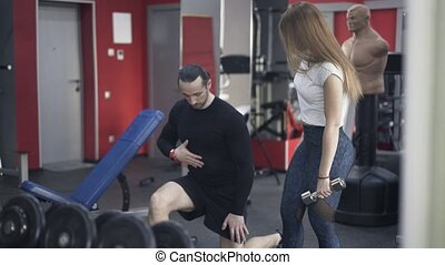 Coach showing woman how to do an exercise in a gym