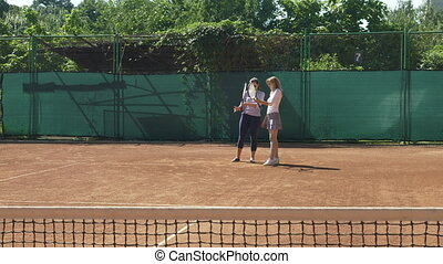 Coach teaches tennis player to hold racket and serve