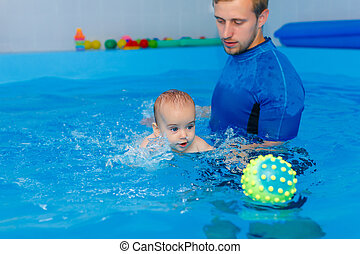 Coach teaches the baby to swim in the pool. baby splash in the water in the pool. The concept of a healthy