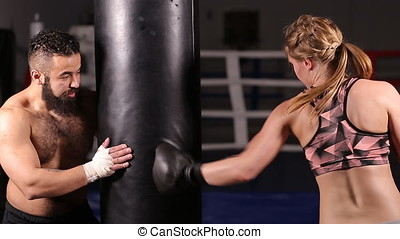 Coach with a student in boxing training. Girl in boxing gloves is working out a blow on the punching pear