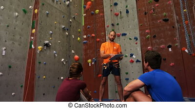 Coach with clip board talking to a man and woman at bouldering gym 4k