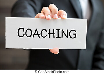 Coaching, message on white card and hold by businessman