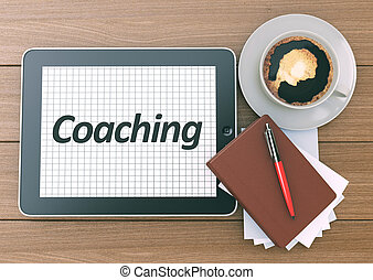 Coaching word on the screen of Digital Tablet PC. Workspace on wooden background. Top view