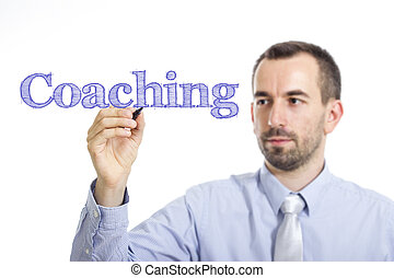 Coaching - Young businessman writing blue text on transparent surface
