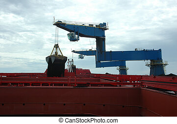 coal is being loaded onto tankers with a blue crane
