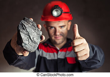 Coal miner with lump of coal - Coal miner showing lump of ...