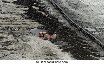 Coal mining in an open pit - huge truck on a coal mine open...