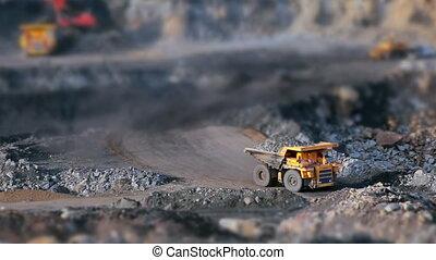 Coal mining in quarry, tilt-shift panorama yellow dump truck carries coal