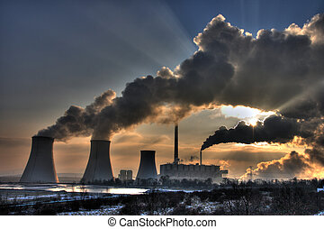 View of coal powerplant against sun with several chimneys and huge fumes