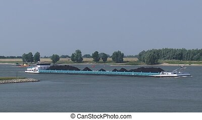 Coal ship upstream on the river Waal + dredger Dintel deepening the fairway