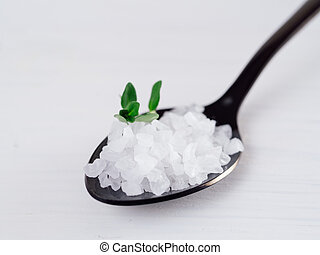 coarse sea salt in black spoon with thyme