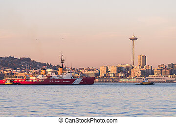 Coast Guard boat in Elliott Bay with sunset over downtown skyscrapers in Seattle, Washington, USA.