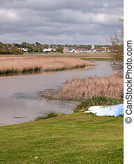 coast line town in the distance behind river with reeds