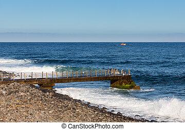 Coast Madeira with jetty and small fishing ship at sea