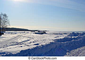 Coast of frozen Onega lake, sunny winter day.