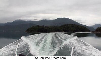 Coast of green mountain river view from boat in Patagonia Argentina.