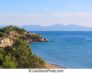 Coast of Mediterranean sea. Beach and rocky wooded shore