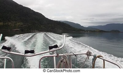 Coast of ocean and green mountain view from boat in Patagonia Argentina.