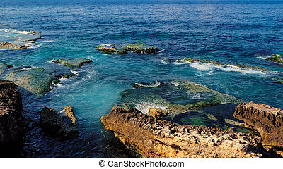 coast with rocks at the sea, clear blue and emerald colored water