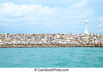 Coastal areas lighthouse. On coastal rocks to roll out into ...