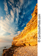 Coastal cliffs and the beach at sunset