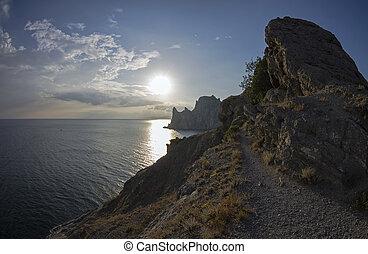 Coastal cliffs illuminated by the evening sun.