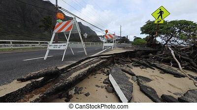 Coastal erosion - waves erode road. Maybe related to rising sea levels, climate change and environmental concerns. From Oahu, Hawaii, USA.