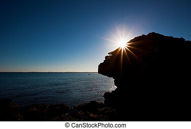 Coastal Morning - Sun Rising over silhouette of rock