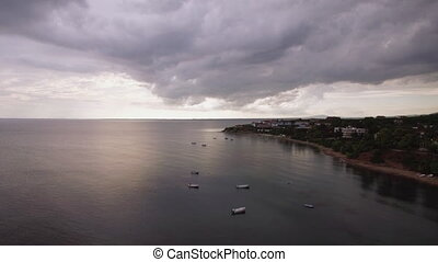 Coastal resort, sea and grey clouds in the sky, aerial. Trikorfo Beach, Greece