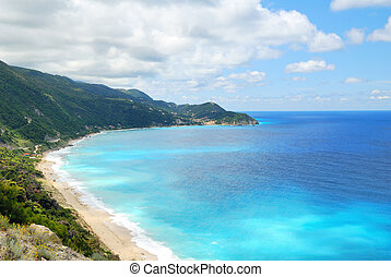 Coastal sea blue waters with beach and steep hill