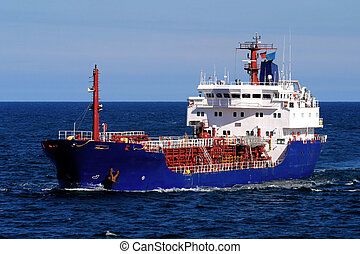 Coastal tanker underway at sea over blue sky and sea.