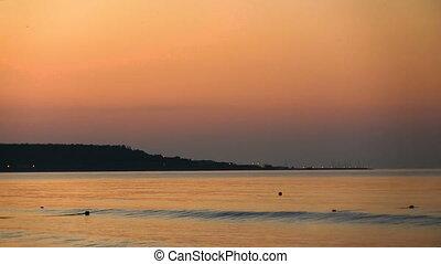 Coastline against the background of the orange dawn. Sea...