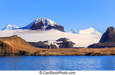 Coastline covered with lots of small gentoo penguins and snow mountains peaks, Barrientos island, South Shetland islands, Antarctic peninsula