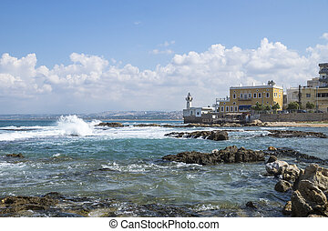 Coastline in Tyre at the ocean with waves and with lighthouse in Tyre, Sour, Lebanon
