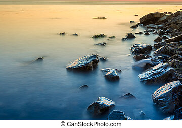 Coastline of the rocky beach of the Black Sea after sunset, Anapa, Russia