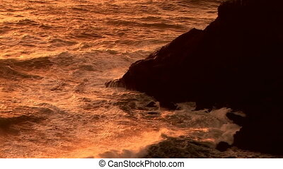 Coastline - Waves roll in at sunset along the rocky Oregon...