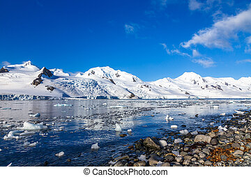Coastline with stones and cold still waters of antarctic sea lagoon with drifting icebergs and snow mountains in the background, Half Moon island, Antarctica