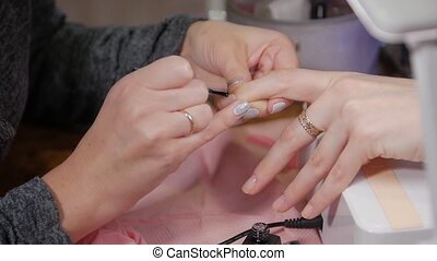 Coating nails with gel polish base manicure closeup