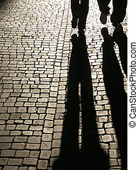 Two people shadows walking on a cobbled street.