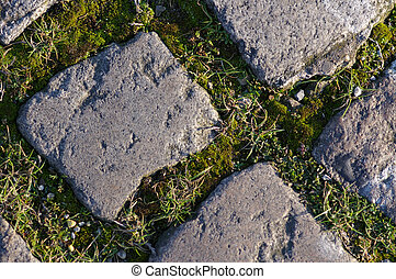 Cobbles with grass in the gaps near the riverside in Liverpool.