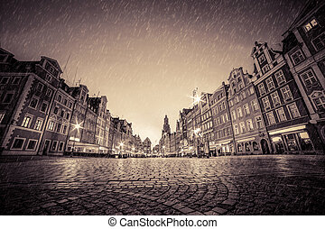Cobblestone historic old town in rain at night. Wroclaw, Poland. Vintage