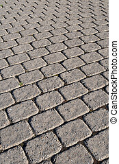 A cobblestone path with square bricks showing perspective.