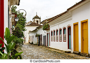 Cobblestone street with old church in the background at Paraty city