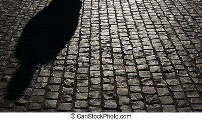 Cobblestoned street at night with shadows and silhouettes of people passing
