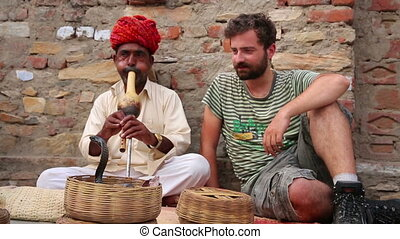 Cobra enchanter sitting in the street with male tourist sitting beside him