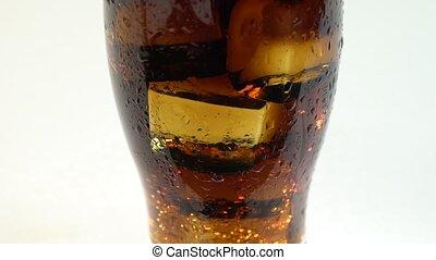 Coca cola in a glass of ice hisses and bubbles. White...